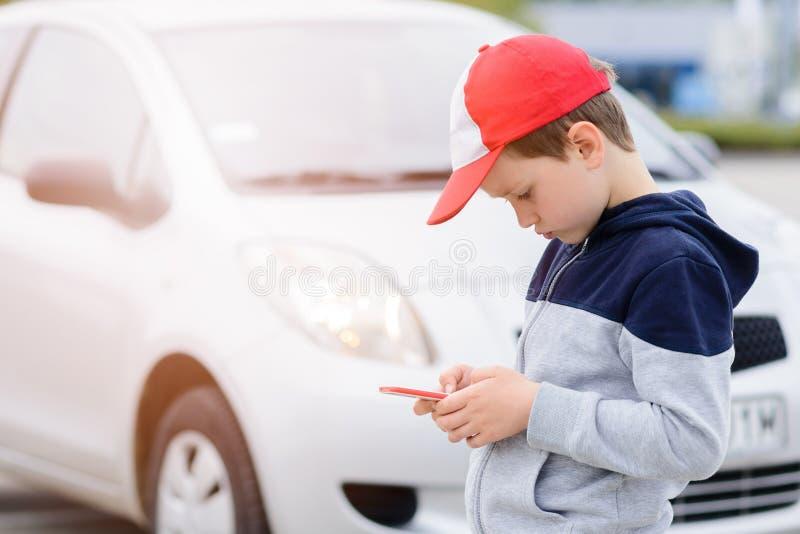 打在智能手机的孩子流动比赛在街道上 库存照片