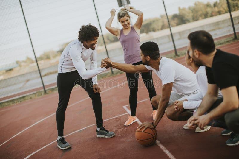 打在法院的不同种族的年轻人篮球 免版税库存图片
