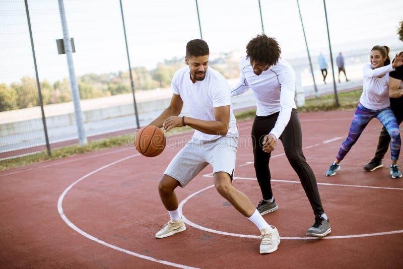 打在法院的不同种族的年轻人篮球 库存照片