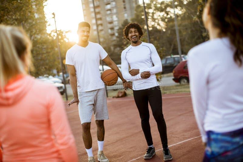 打在法院的小组不同种族的年轻人篮球 免版税库存图片
