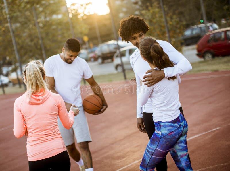 打在法院的小组不同种族的年轻人篮球 免版税图库摄影