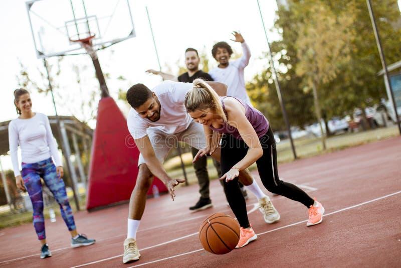 打在法院的小组多种族年轻人篮球在户外 免版税库存图片