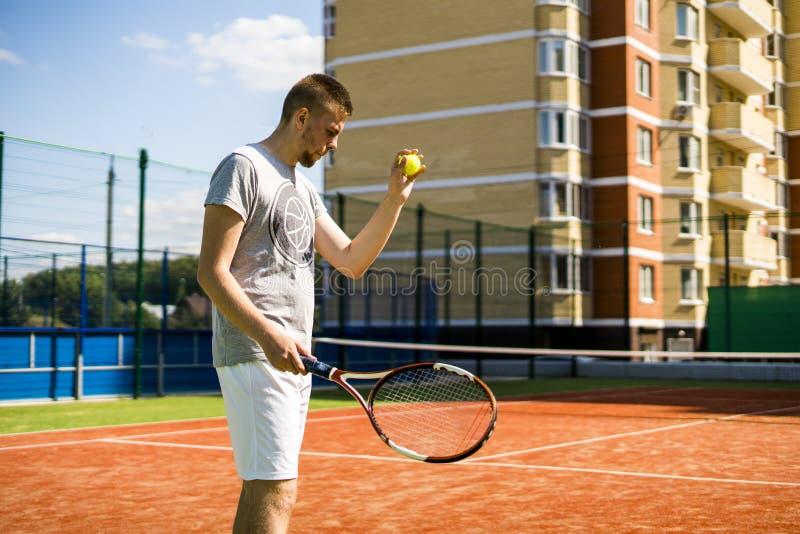 打在法院的年轻人网球在室外的公寓单元围场 免版税图库摄影