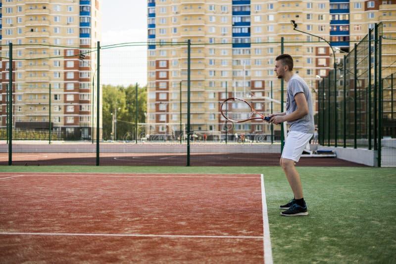 打在法院的年轻人网球在室外的公寓单元围场 免版税库存照片