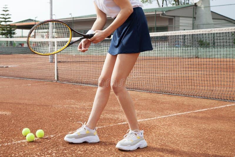 打在法院的年轻女人网球 库存图片