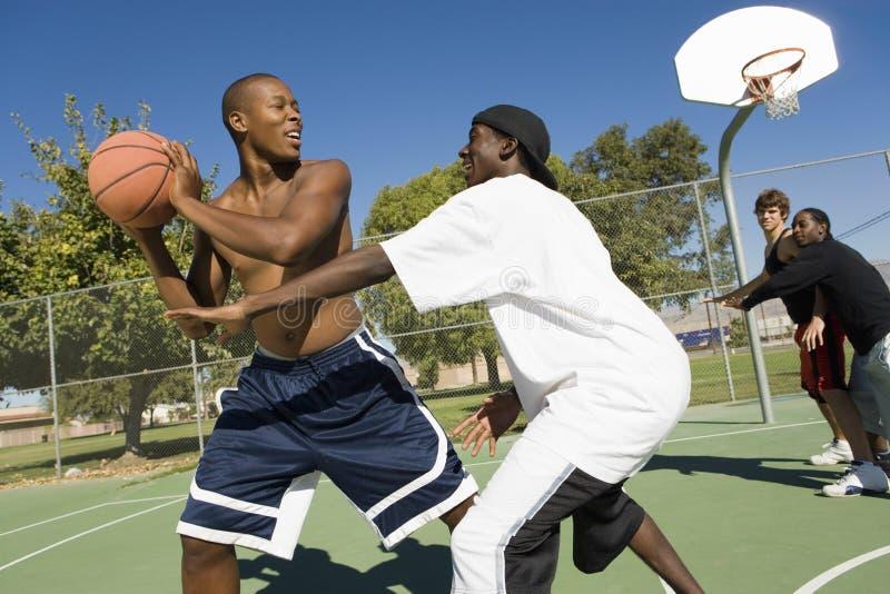 打在法院的朋友篮球 免版税库存照片