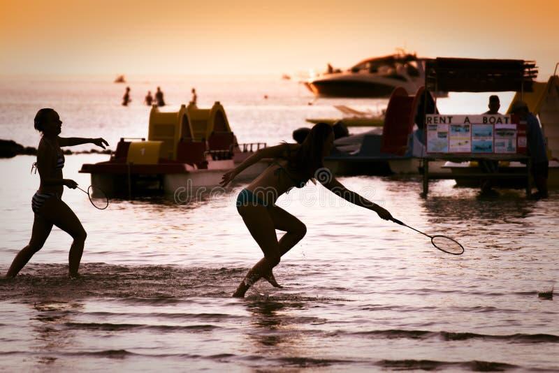 打在海滩的由后面照的女孩羽毛球在日落 库存图片