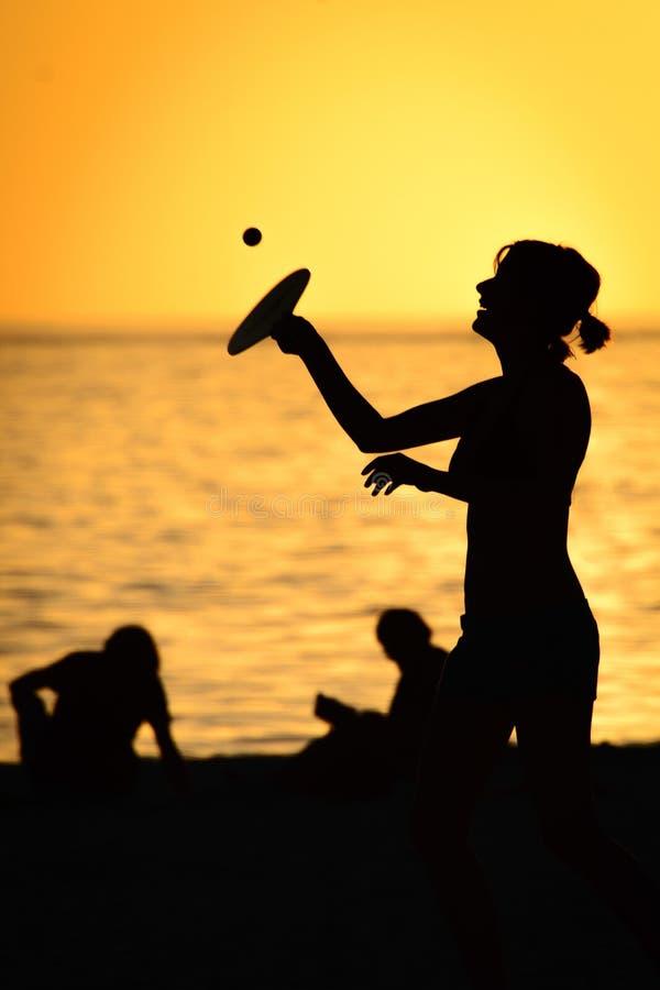 打在海滩的妇女桨球 免版税库存图片