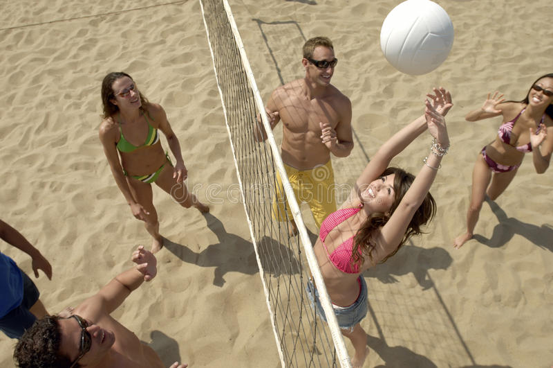 打在海滩的青年人排球 免版税库存图片