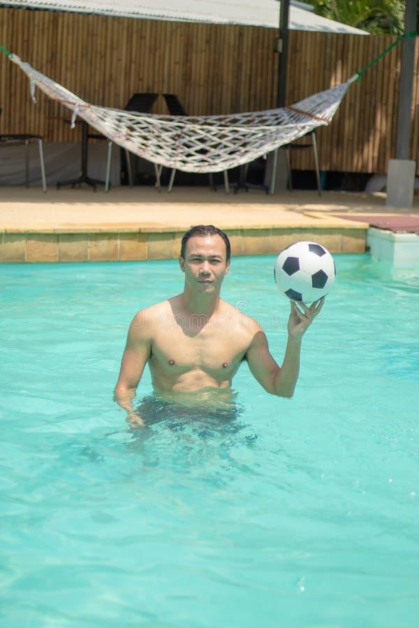 打在游泳场的人足球 免版税图库摄影