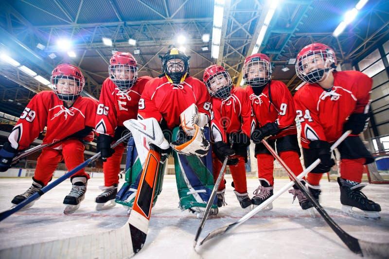 打在溜冰场的孩子冰球 免版税库存照片