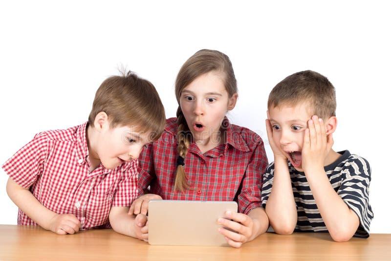 打在片剂的小组孩子扣人心弦的比赛隔绝在白色 免版税库存照片
