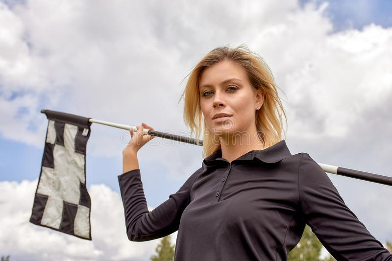 打在绿色领域户外背景的美女的画象高尔夫球 高尔夫球的概念,追求  免版税图库摄影