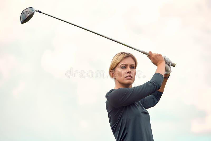 打在绿色领域户外背景的美女的画象高尔夫球 高尔夫球的概念,追求  库存照片