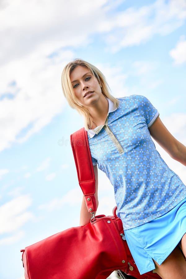 打在绿色领域户外背景的美女的画象高尔夫球 高尔夫球的概念,追求  免版税库存照片