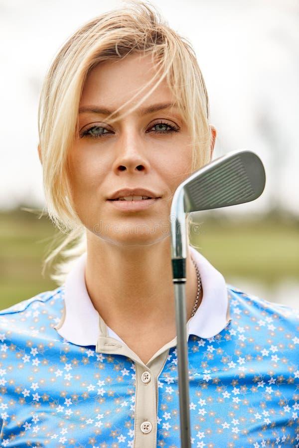打在绿色领域户外背景的美女的画象高尔夫球 高尔夫球的概念,追求  图库摄影