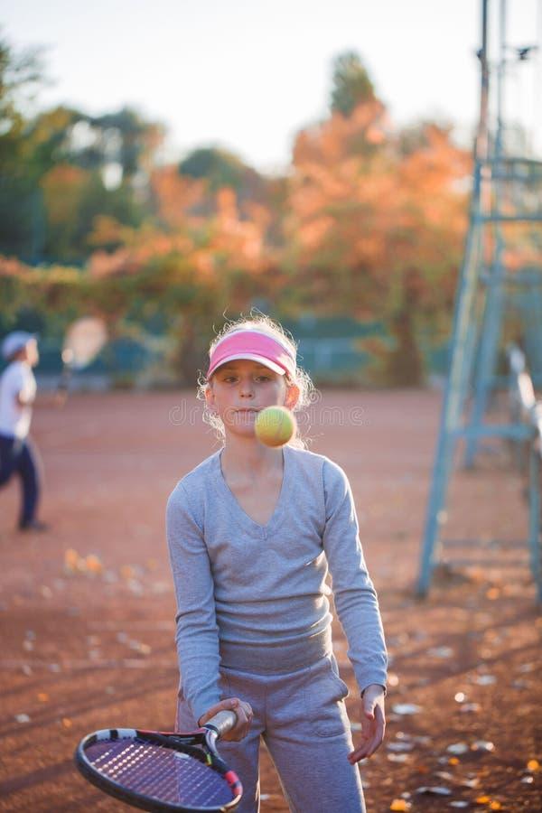打在网球场的一个十几岁的女孩网球 免版税库存图片