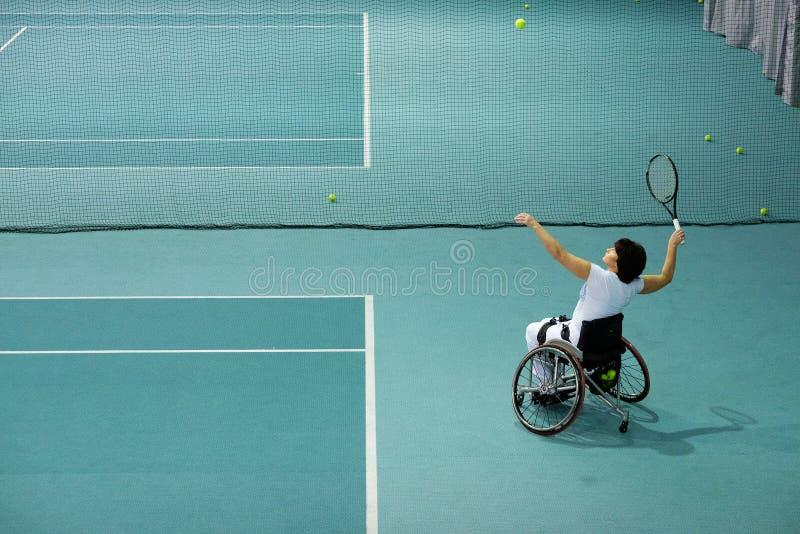 打在网球场的轮椅的残疾成熟妇女网球 免版税库存照片