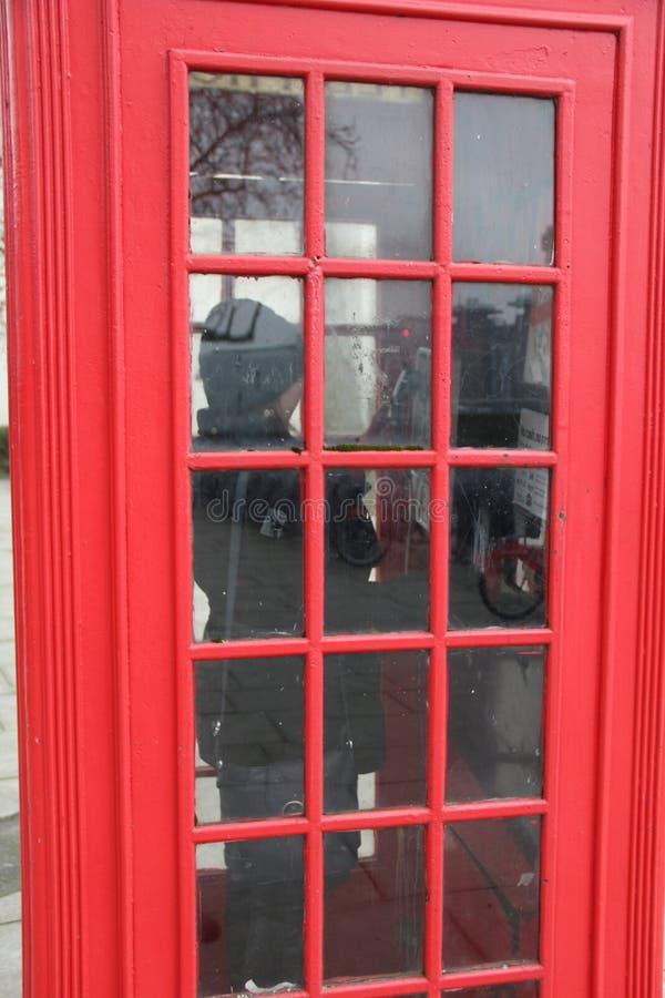 打在英国红色PhoneBox的女性一次电话 库存图片