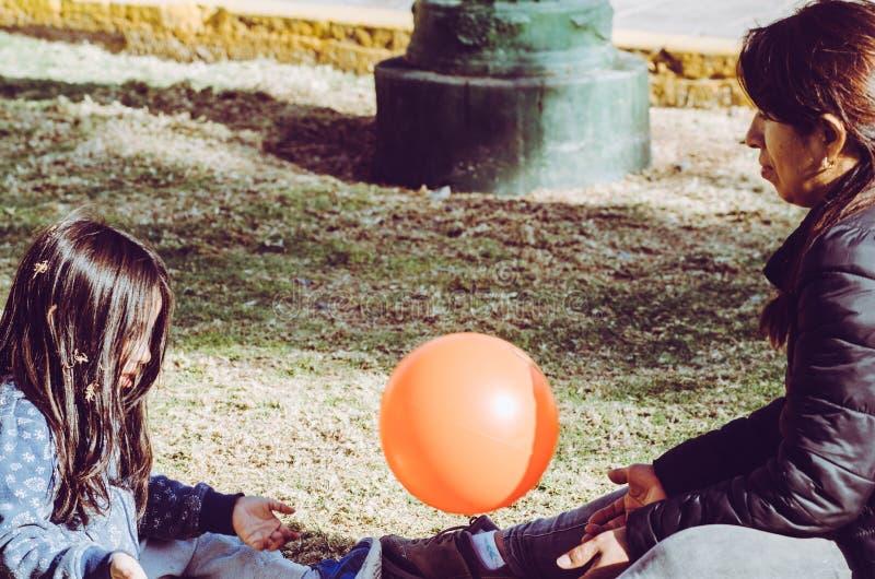 打在草的母亲和女儿球在公园 库存照片