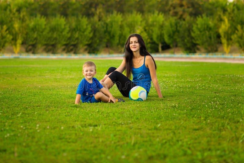 打在草的母亲和小儿子球在公园 免版税库存照片