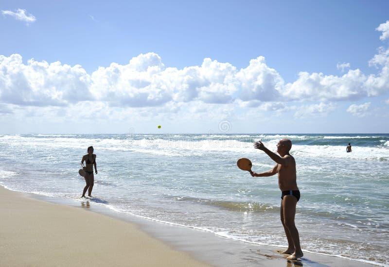 打在萨包迪亚海滩的少妇海滩网球 免版税库存照片