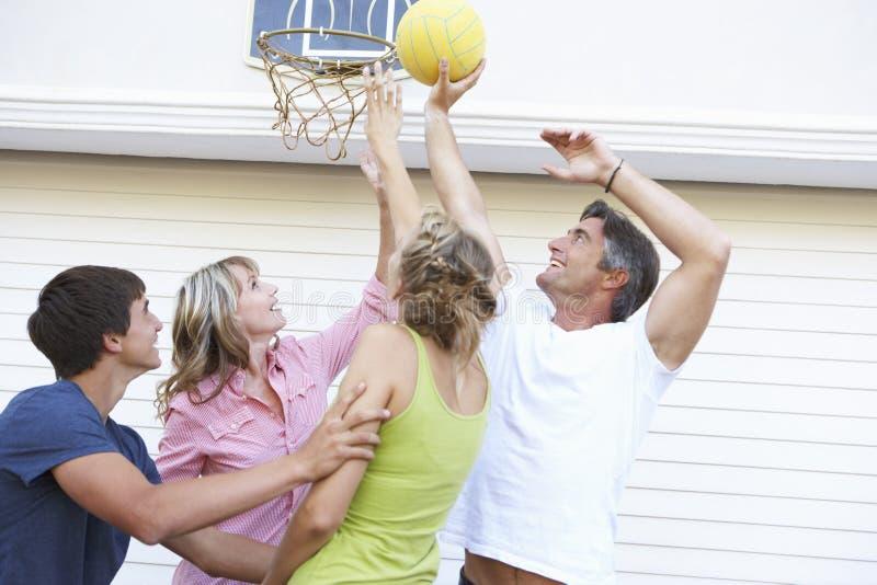 打在车库之外的少年家庭篮球 免版税库存照片