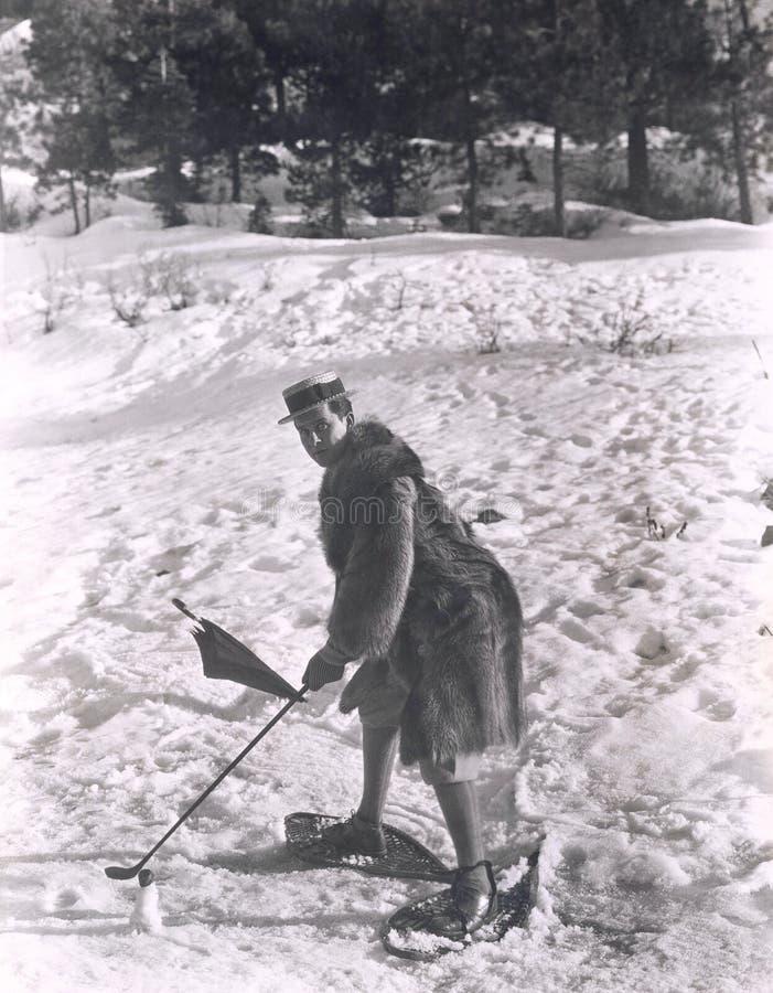 打在雪的人高尔夫球 库存照片
