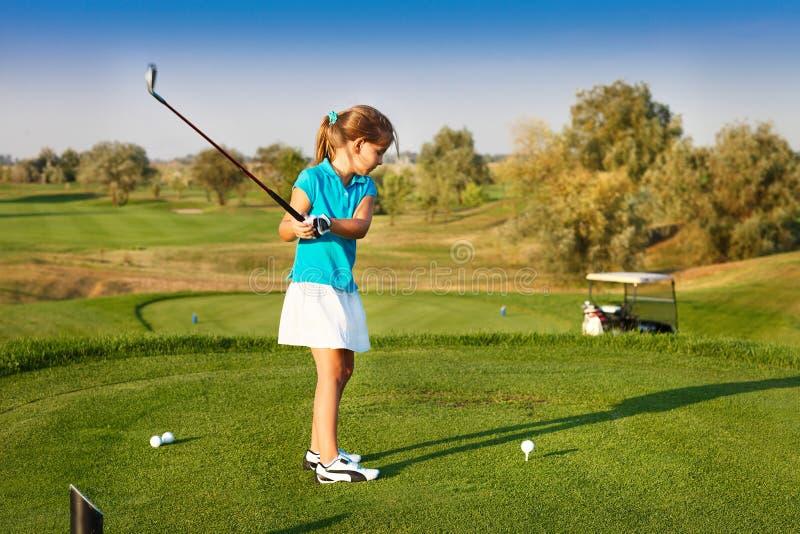 打在领域的逗人喜爱的小女孩高尔夫球室外 免版税库存图片