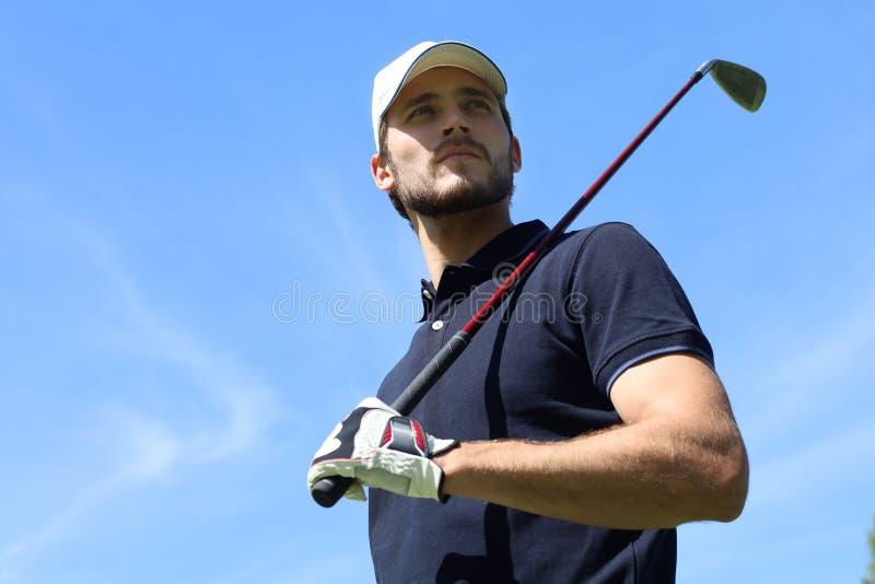 打在高尔夫俱乐部的运动年轻人高尔夫球 库存照片