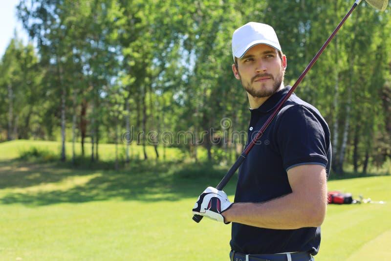 打在高尔夫俱乐部的运动年轻人高尔夫球 免版税库存图片