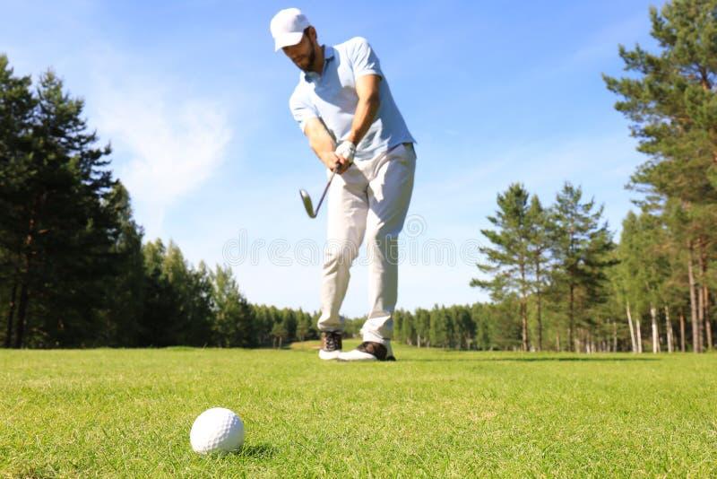 打在高尔夫俱乐部的运动年轻人高尔夫球 库存图片