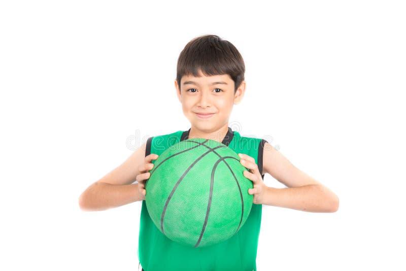打在绿色PE制服体育的小男孩绿色篮球 免版税库存照片