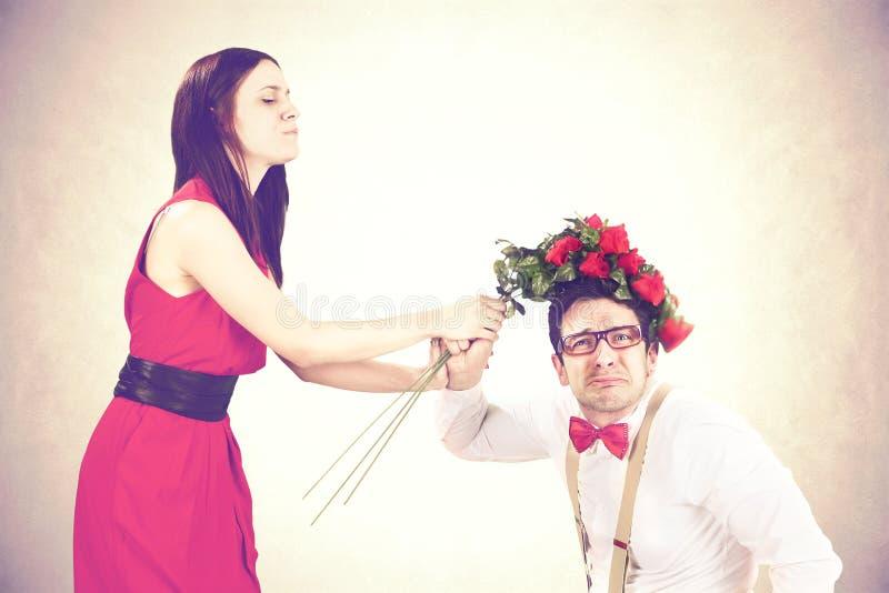 打她的有玫瑰的愤怒的妇女男朋友 免版税库存图片