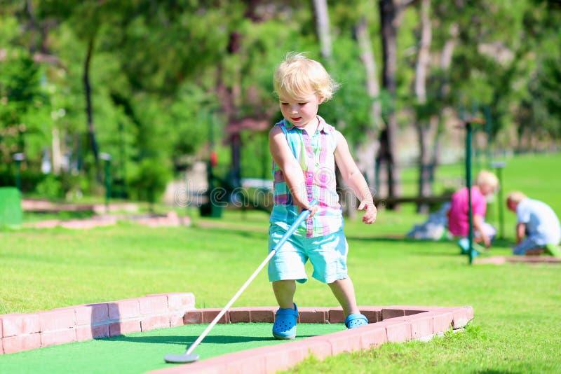 打小小高尔夫球的孩子外面 库存照片