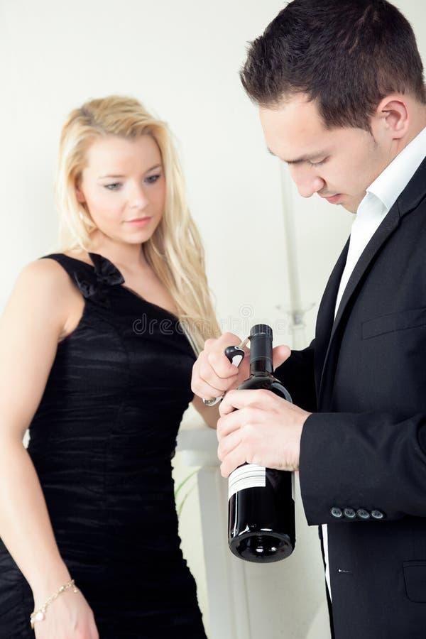 打开一个瓶红葡萄酒的人 图库摄影