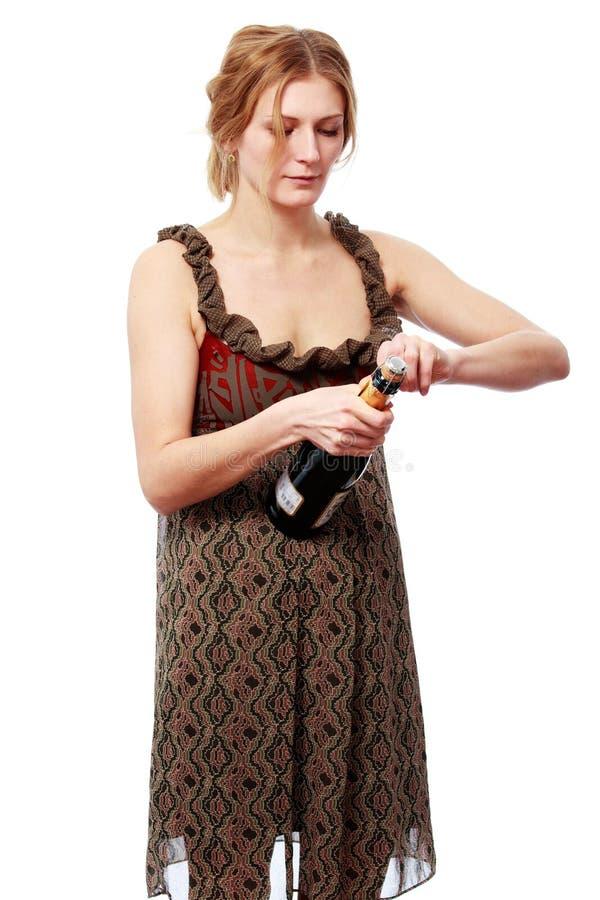 打开一个瓶香槟的明亮的礼服的妇女 免版税图库摄影