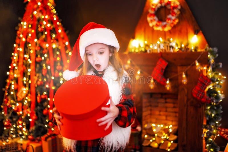 打开一件不可思议的圣诞节礼物的可爱的小女孩由一棵圣诞树在舒适客厅在冬天 图库摄影