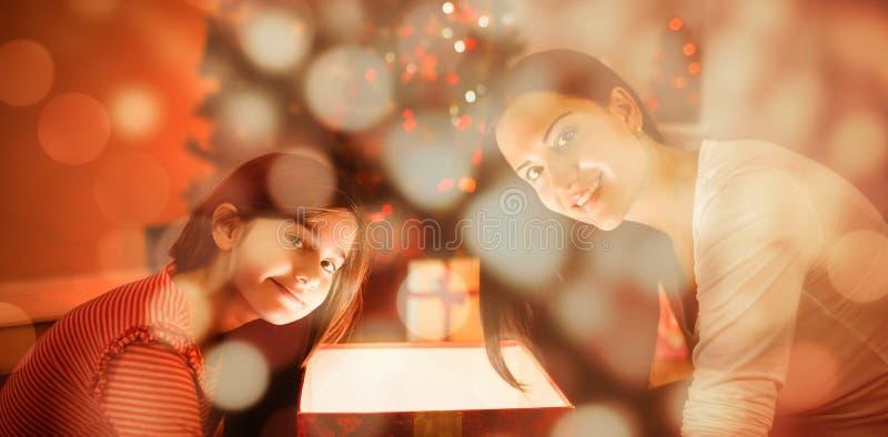 打开一件发光的圣诞节礼物的欢乐的母亲和女儿的综合图象 免版税库存图片