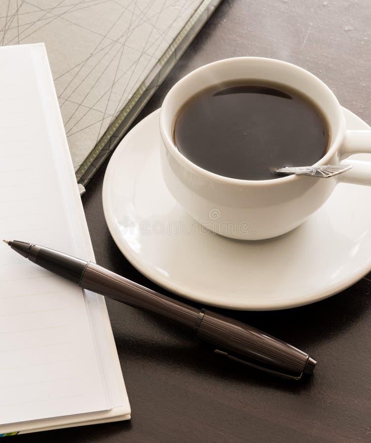 打开一杯空白的白色笔记本、笔和咖啡 库存照片