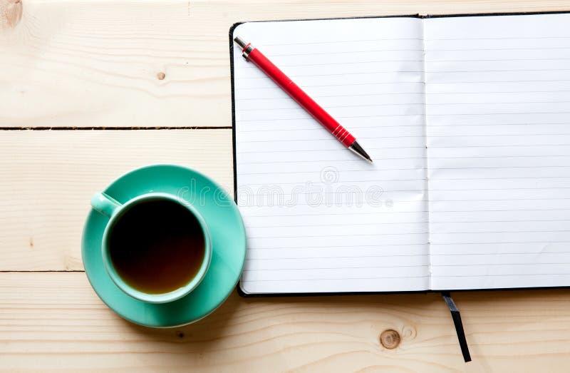 打开一杯空白的白色笔记本、笔和茶在书桌上的 图库摄影