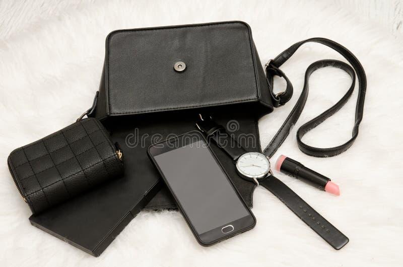 打开与下降的事、手机、手表、钱包和唇膏的黑袋子 在背景,顶视图的白色毛皮 时尚concep 库存照片