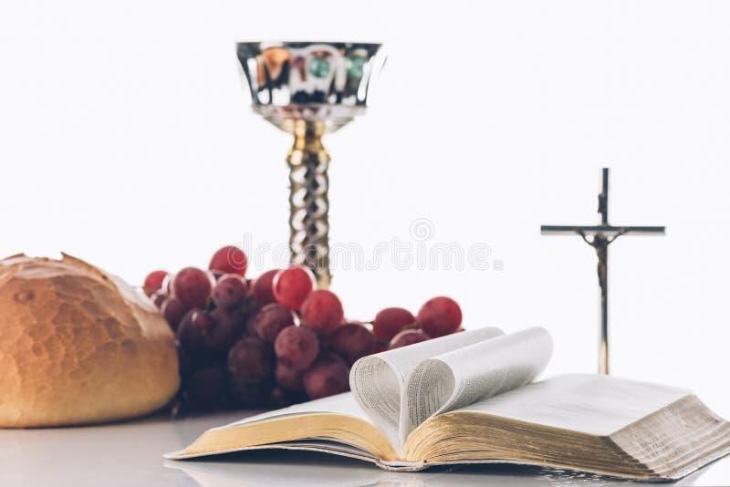 打开与基督徒十字架的在桌上的圣经和酒杯, 免版税库存照片