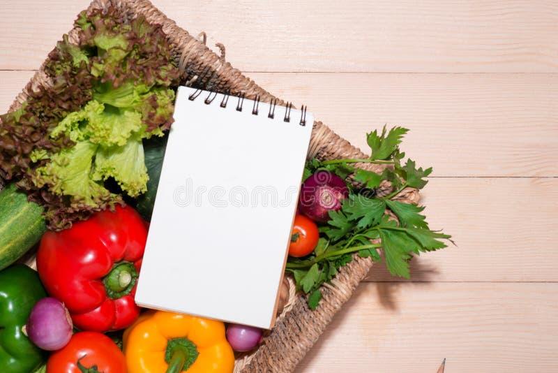 打开与有机素食成份的食谱书 免版税库存图片