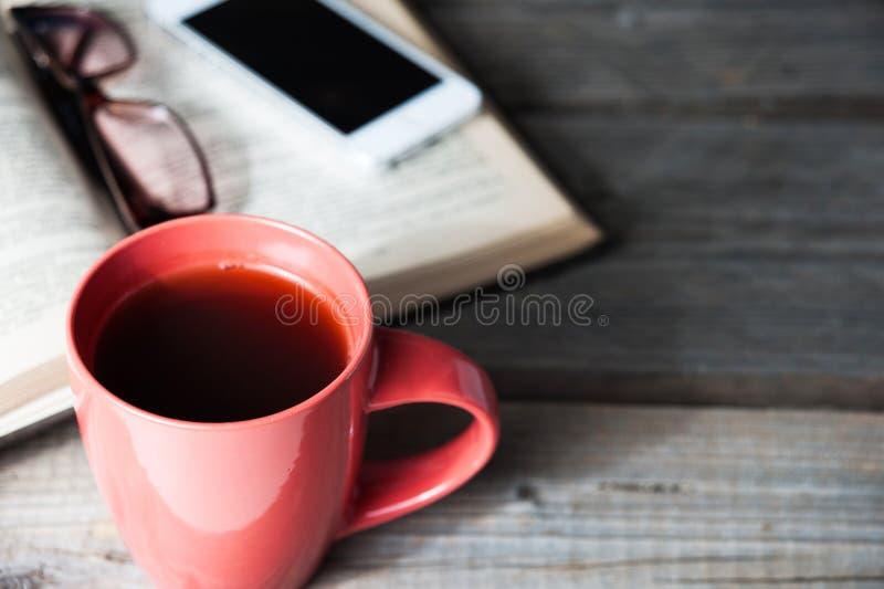打开与电话的书、玻璃和咖啡或者茶顶视图在桌上 免版税库存图片