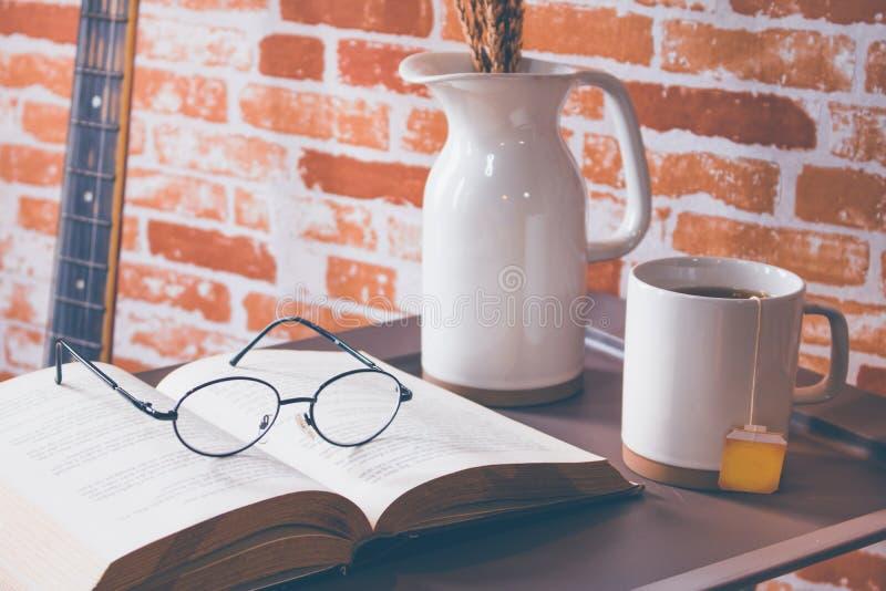 打开与眼睛玻璃的书在桌和茶上 免版税库存图片