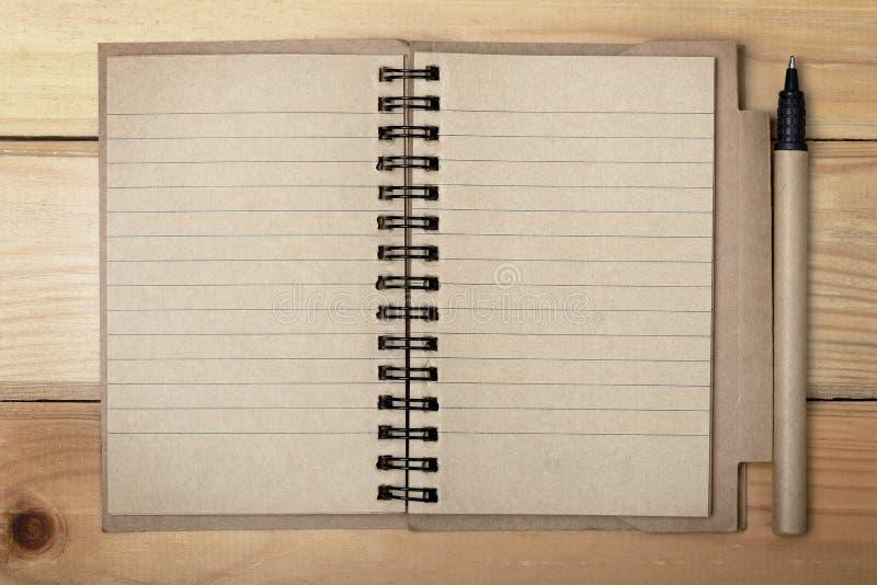打开与笔的纸笔记本在木背景 免版税图库摄影