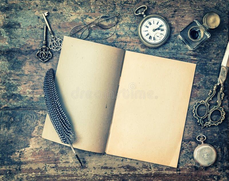 打开书和葡萄酒文字在木桌上 被定调子的减速火箭的样式 库存图片