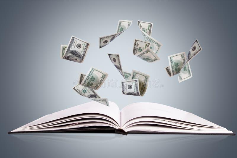 打开书或杂志与飞行的美元钞票 免版税库存图片
