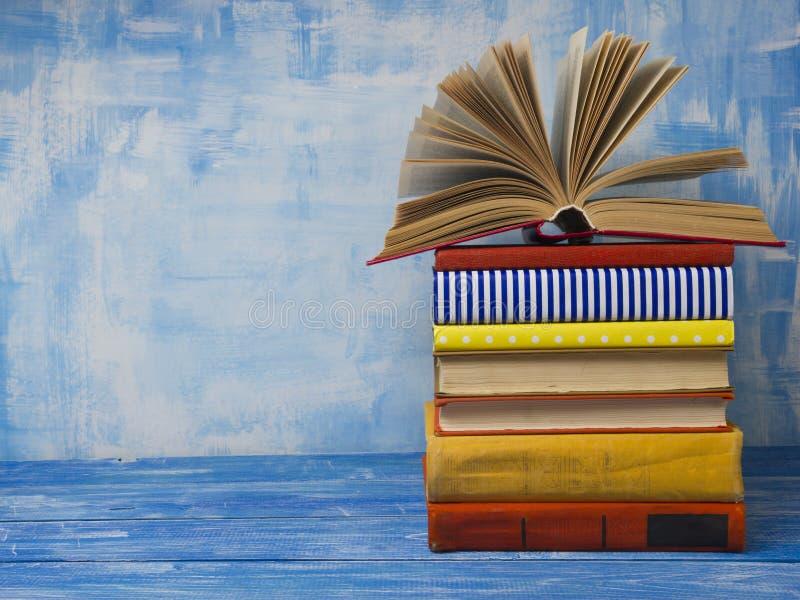 打开书,在抽象蓝色背景的精装书书在木桌上 回到学校 复制文本的空间 库存图片